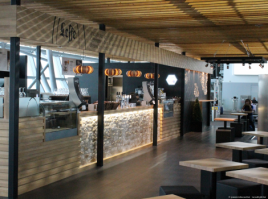 Bar in airport with several design lamps in wood