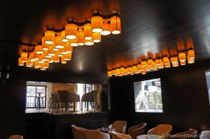 bespoke ceiling lights in maple wood in basement above tables for a wine bar in gent